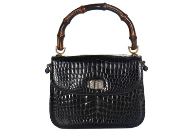 Lot 8-A fine and rare Gucci ink-blue crocodile handbag with bamboo handle, 1960s