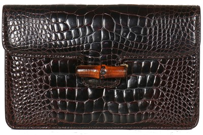 Lot 10-A Gucci brown crocodile clutch bag with bamboo lift-clasp, early 1970s