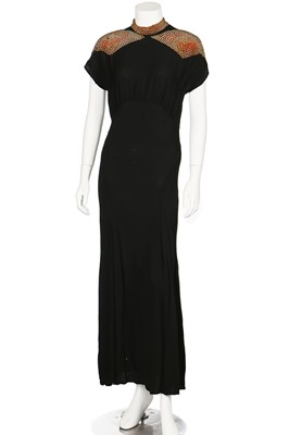 Lot 71-A black crêpe evening-gown with studded red and purple angular insertions to shoulders, mid 1940s