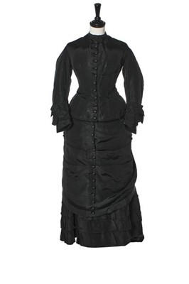 Lot 282 - A black faille mourning gown, late 1870s,...